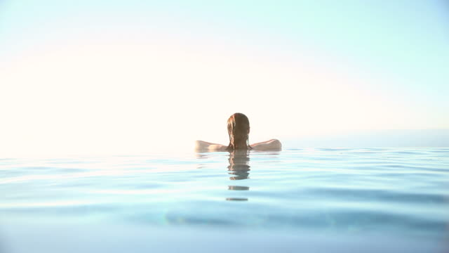 Woman resting on edge of infinity pool video