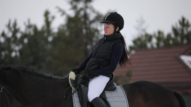 woman rider walking horseback with horse at winter snowy day - siodło filmów i materiałów b-roll