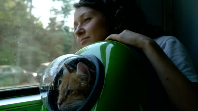 Woman rides a train with a red cat in a backpack with a porthole - vídeo