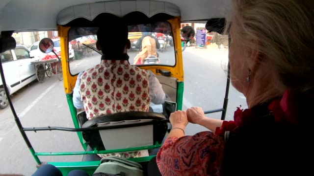 Woman rides in tuk-tuk rickshaw with driver