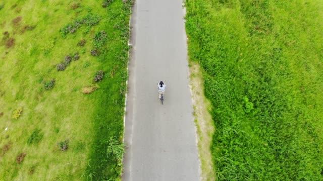 川の近くの道路で自転車に乗る女 - サイクリング点の映像素材/bロール