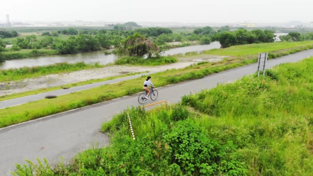 Woman riding a bicycle on a road near a river