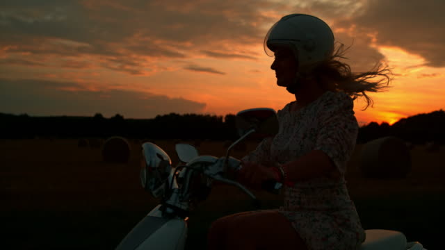 SUPER SLO MO Woman riding a scooter at sunset