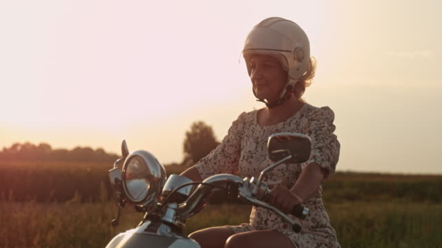 SUPER SLO MO Woman riding a scooter in the country at sunset