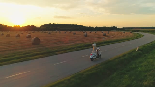 AERIAL Woman riding a scooter in the country at sunset
