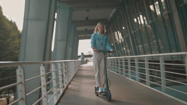 woman riding electric kick scooter on footbridge - monopattino elettrico video stock e b–roll