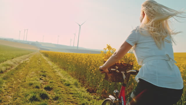 slo mo woman riding her bicycle along field of canola with wind turbines in the distance - energia rinnovabile video stock e b–roll