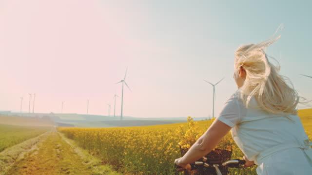 super slo mo - time warp effect donna in sella alla sua bicicletta lungo il campo di canola con turbine eoliche in lontananza - canola video stock e b–roll