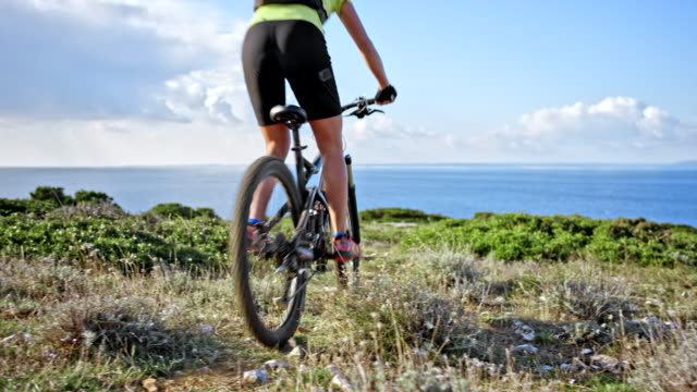 woman riding her bike down a hill with a beautiful view of the sea - andare in mountain bike video stock e b–roll