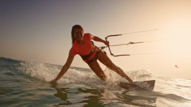 SLO MO Woman riding her kiteboard with one hand in the water and smiling into the camera at sunset