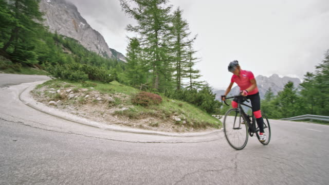 woman riding her road bike up the asphalt road high in the mountains on a cloudy day - ciclismo su strada video stock e b–roll