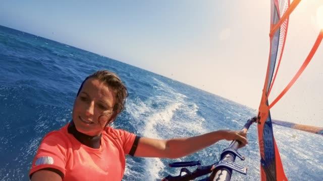 LD Woman riding her windsurf in sunshine