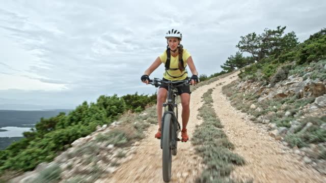 woman riding mountain bike down the mountain on a gravel road - pantaloncini video stock e b–roll