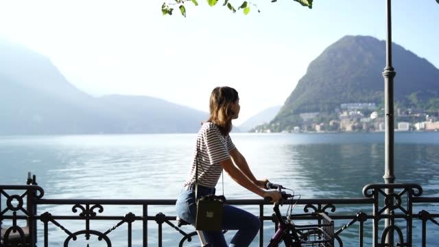 vídeos de stock e filmes b-roll de woman riding on a bicycle along a scenic lakeside - suíça