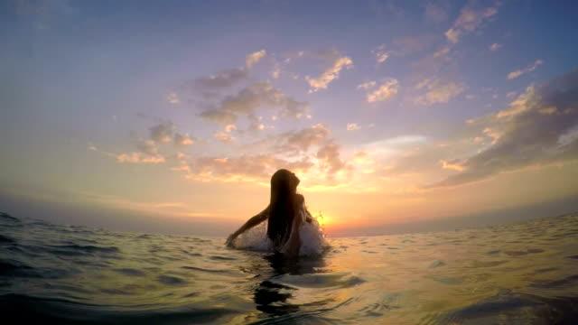 Mujer aumenta desde el mar en la puesta de sol - vídeo