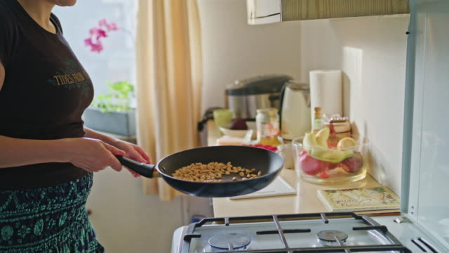 woman roasting peanuts in a pan - сковорода стоковые видео и кадры b-roll