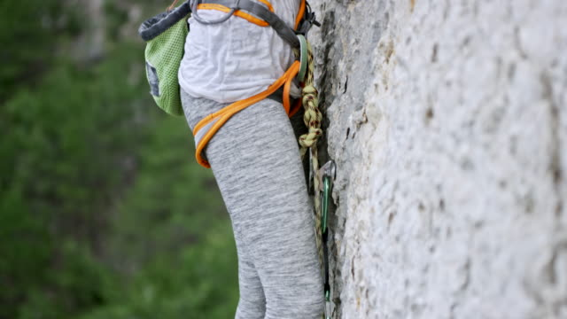 vídeos y material grabado en eventos de stock de trepando por el acantilado de la roca de tu mujer - escalada en rocas