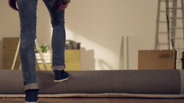Woman rolling out carpet in new apartment Medium shot of woman rolling out a carpet in her new apartment. She pushes the carpet with her feets. Camera behind the woman moves foreward. rolling stock videos & royalty-free footage