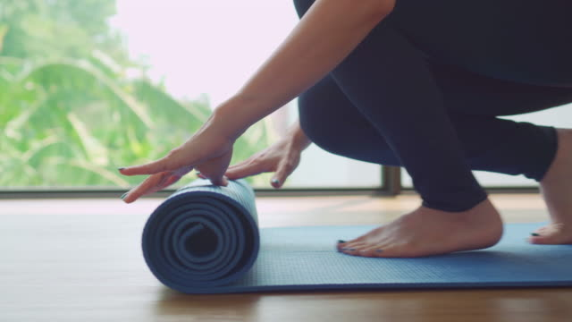 woman rolling out yoga mat and preparing to meditate training in yoga - tappetino video stock e b–roll