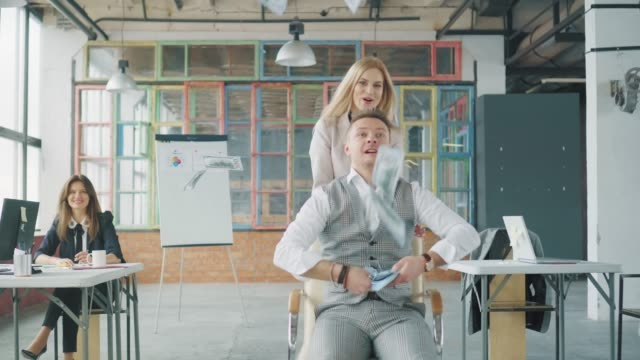 A woman rolls a man colleague in an office chair. A man throws up money, they laugh and have fun. Employees ride on a chair around the office. Co-working. Office life. Creative interior video