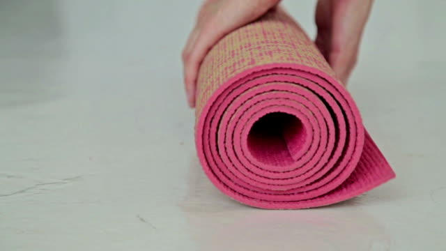 woman rolls apart yoga mat in fitness studio - tappetino video stock e b–roll