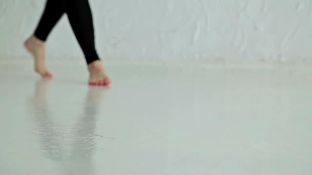 Woman rolls apart yoga mat in fitness studio video