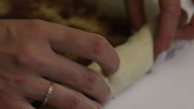 a woman rolls rolled dough for cinnabons. shot in close up, cinnamon and sugar are visible. - formare pane video stock e b–roll