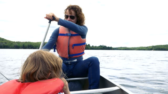 Woman Rowing a Boat with a Child Seated in Front video