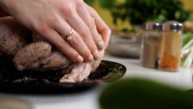 女性はオーブンで焼くためにそれを置く前に塩とコショウで全体の鶏をこすります。 - 自家製点の映像素材/bロール