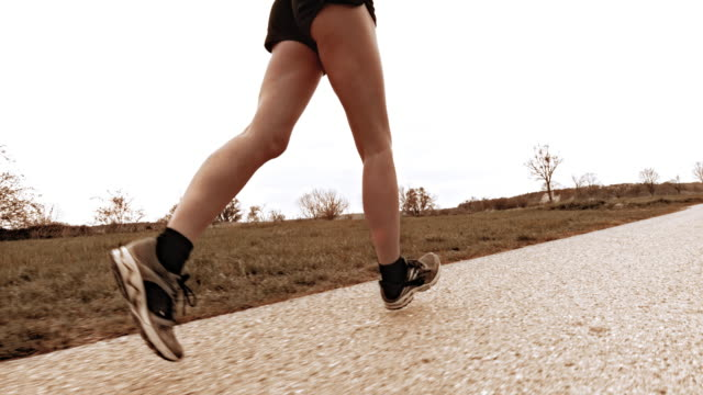 SLO MO TS Woman runner running along countryside road video