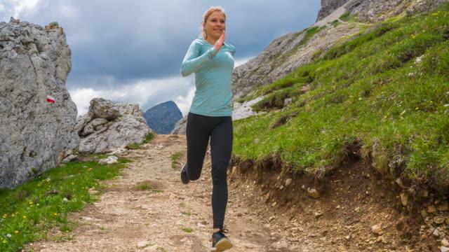 山道のオフロードを実行する女性ランナー - チロル州点の映像素材/bロール