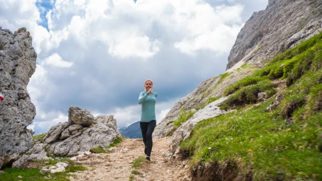 vídeos de stock, filmes e b-roll de mulher corredora correndo fora da estrada em caminhos de montanha - tyrol state austria