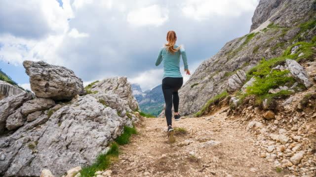 frau läufer läuft über felsige pfade in alpinem gelände - hinter stock-videos und b-roll-filmmaterial