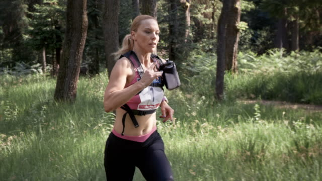slo mo ds woman running a trail marathon amongst the forest trees - leanincollection stock videos & royalty-free footage