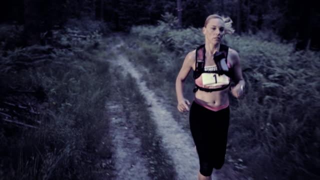 slo mo ds donna di correre una maratona da trail al tramonto - competizione video stock e b–roll