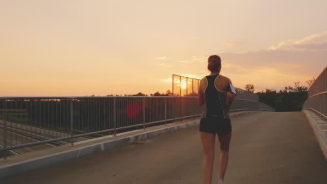 stockvideo's en b-roll-footage met slo mo vrouw lopen over een brug bij zonsondergang - bovenkleding