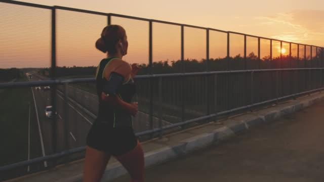 日没時の高速道路橋を渡って流れて slo mo 女性 - スロベニア点の映像素材/bロール