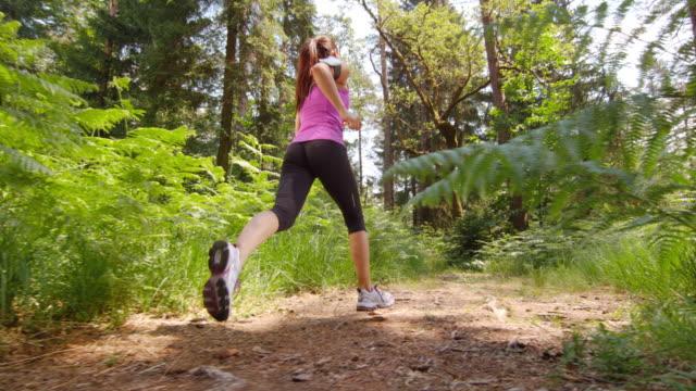 MO DS de San Luis Obispo de mujer corriendo en el bosque de compensación en el sol - vídeo