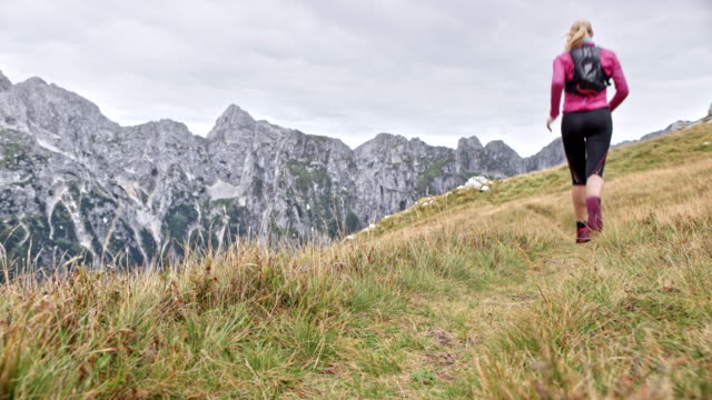 LD Woman running across a grassy mountain ridge in the high mountain range Wide locked down low angle shot of a woman running across a grassy trail across a ridge high in the mountains. Shot in Slovenia. pedal pushers stock videos & royalty-free footage