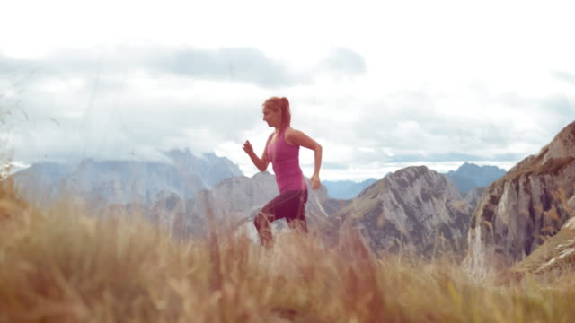 SLO MO DS Woman running across a meadow overlooking the mountains Slow motion wide low angle dolly shot of a woman running across a meadow high in the mountains with a nice view on the nearby peaks. Shot in Slovenia. pedal pushers stock videos & royalty-free footage