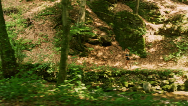 SLO MO Woman running across a small bridge in a forest