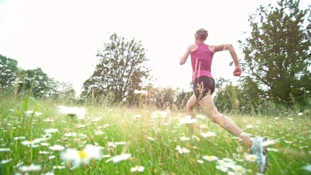 vidéos et rushes de slo mo ts femme courant à travers l'herbe haute - joggeuse