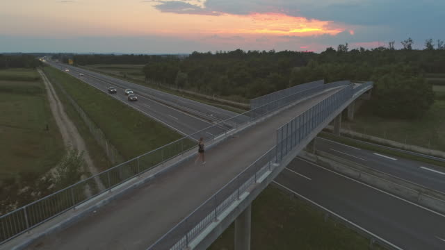 AERIAL Woman running across the bridge at dusk