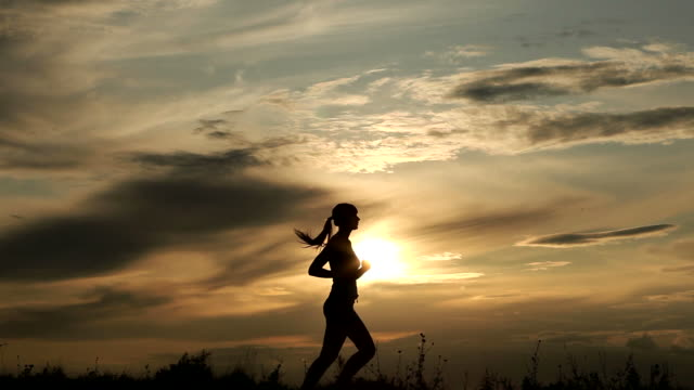 Woman Running against sunset A woman running against sunset lockdown viewpoint stock videos & royalty-free footage