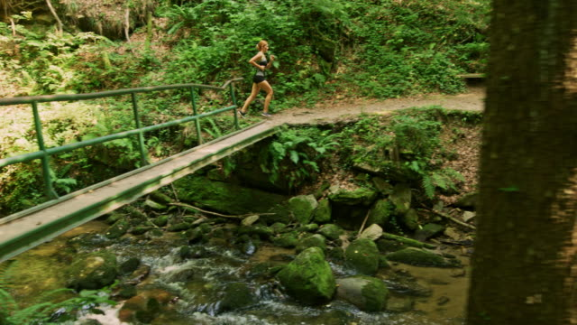SLO MO Woman running along a stream in the forest