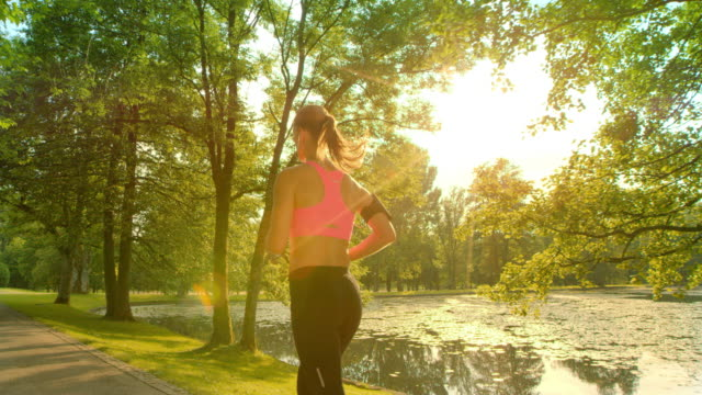 SLO MO TS Woman running along lake in sunshine video