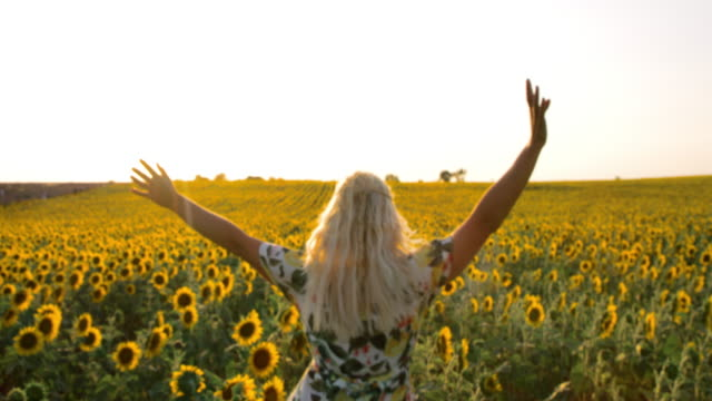 WS Woman running among sunflowers in the field