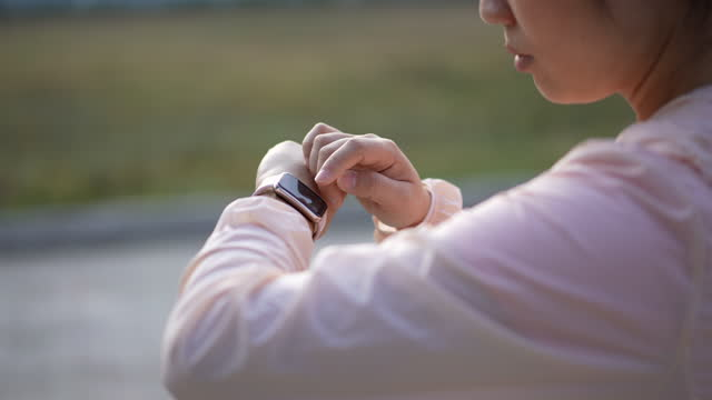 Woman running and checking smartwatch for monitoring her running performance
