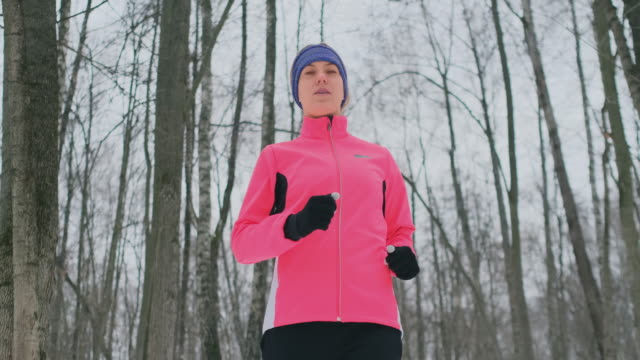 Woman Running at snowly winter under sunlight