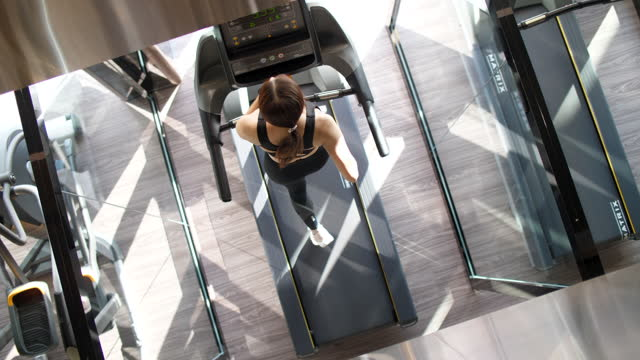 Woman Running at Treadmill ,New Normal and Modern Gym Social Distancing GYM apply for people living in the COVID-19 health club stock videos & royalty-free footage